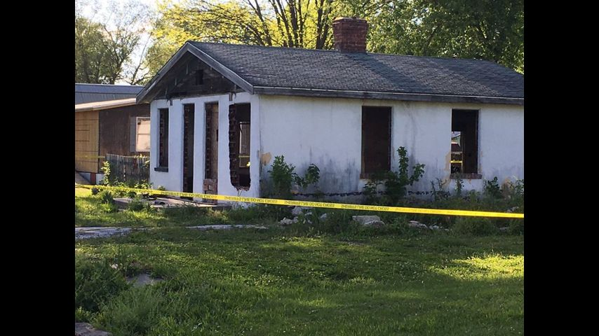An abandoned house in Vandalia is cordoned off by police tape after unidentified human remains were found. The building, on Limit Street, is owned by John Lue, who was taken into custody.