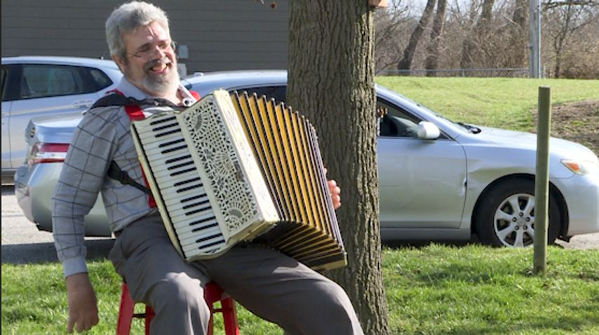 Scott Denson plays his accordion for neighbors and strangers at a distance to uplift spirits during the COVID-19 pandemic.