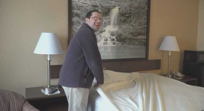 James White makes a bed at Super 8 in Boonville where he's known as Superman.
