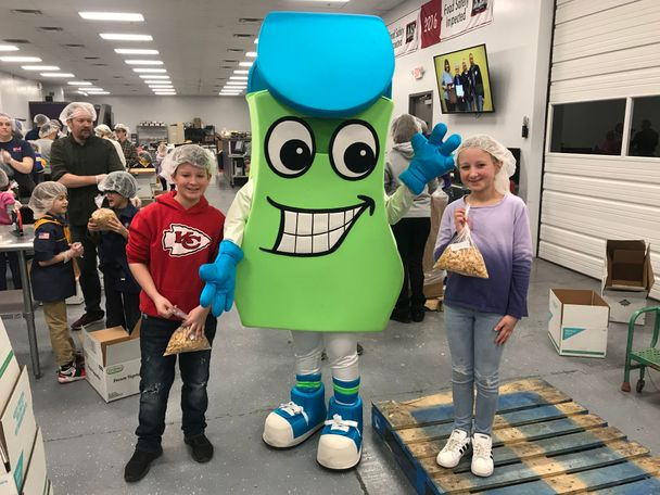 Buddy, the buddy pack mascot, takes a quick pic with two volunteers.