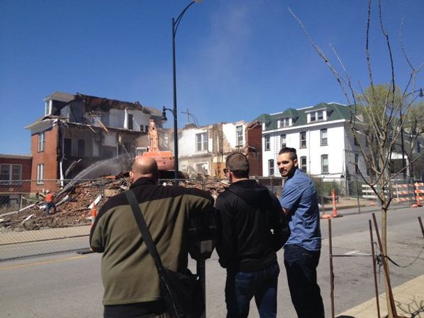 Bystanders standing near the demolition site.