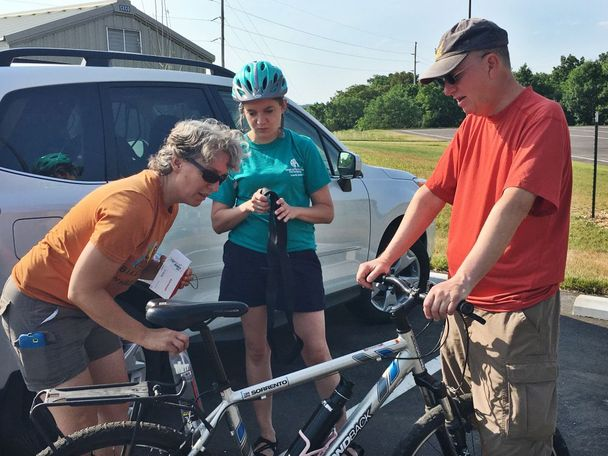 Teacher Rachel Ruhlen looks at Gretchen Maune's bike seat as Gretchen feels an inner tube to help further understand her bike. Teacher Joe Silsby looks on as he holds up Gretchen's bike. All three are on the PedNet Coalition.