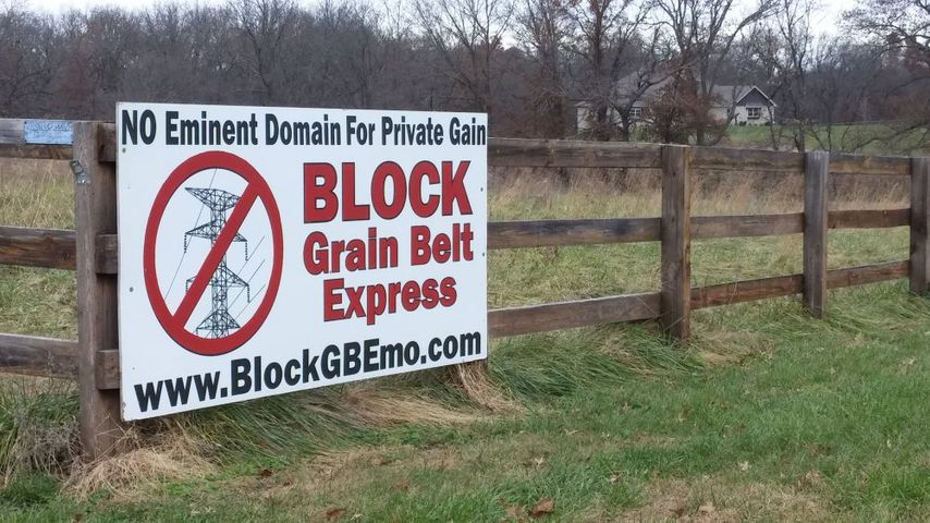 A sign along the road urges people to oppose the proposed transmission line.