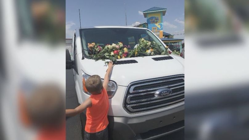 One of Reid's sons laying flowers on a car left behind in the parking lot of Ride the Ducks.