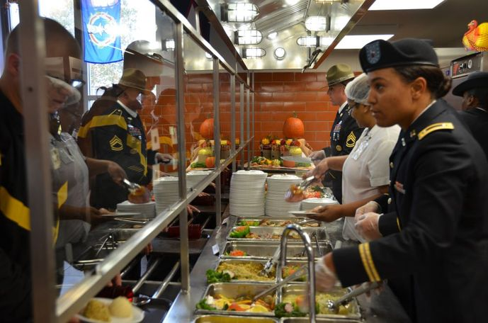 Soldiers in training at Fort Leonard Wood go through the serving line where commanders, first sergeants and other senior leaders take time out to serve Thanksgiving meals.