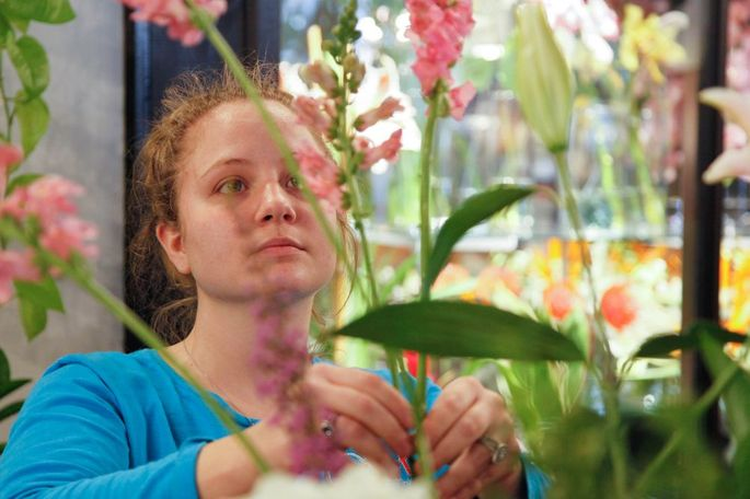 """Taylor Mountjoy, a flower designer, arranges flowers in My Secret Garden in Columbia, Missouri on Sunday, Feb. 12, 2017. Ruth LaHue said the goal of My Secret Garden is to """"share the beauty of flowers on a daily basis."""""""