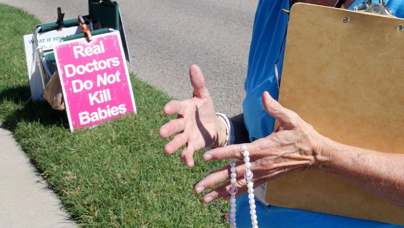 Carol Fick holds her rosary outside of Planned Parenthood in Columbia, Mo., on Monday, Sept. 30, 2019. The group held many signs like the one depicted outside of the clinic as a part of 40 Days for Life.