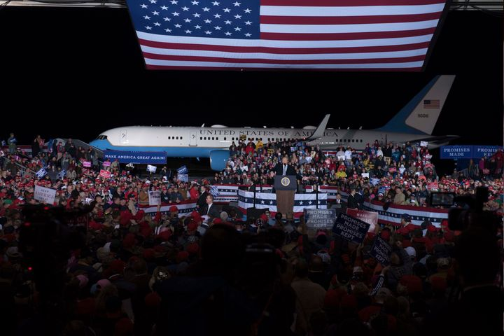 An enormous American flag flies over President Donald Trump as he wraps up a speech to a capacity crowd at Columbia Regional Airport.