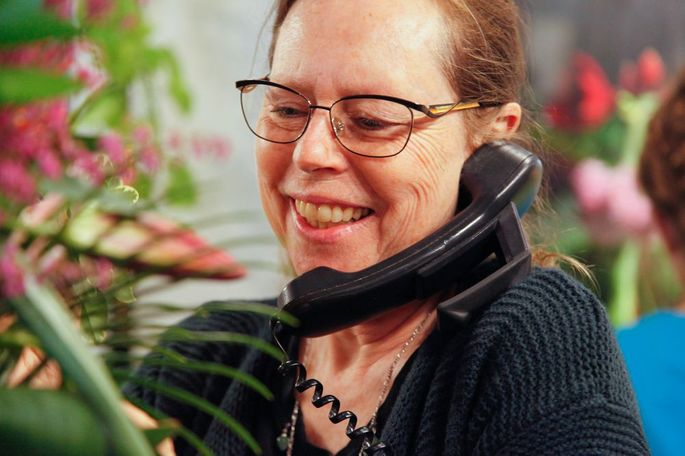 """Ruth LaHue, owner of My Secret Garden, calls a new employee to set up a training schedule in My Secret Garden in Columbia, Missouri on Sunday, Feb. 12, 2017. She stopped working with all wire services in 2016. """"I'm a florist because I want to make people happy. I want to help the person and it takes that all out,"""" she said."""